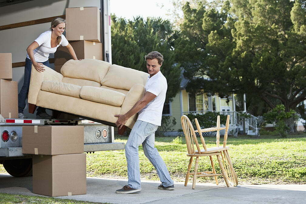 Couple moving house, loading or unloading couch in moving van